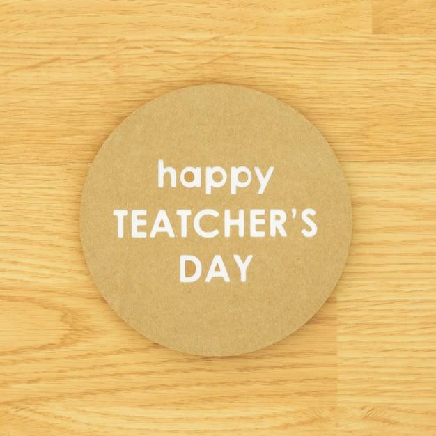 Buon giorno dell'insegnante in un cerchio su fondo di legno Foto Gratuite