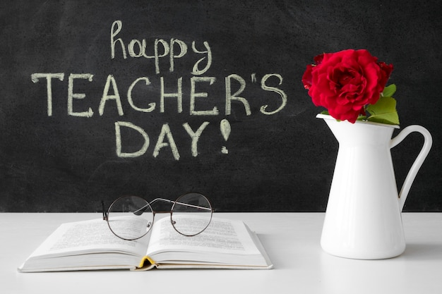 Felice giornata dell'insegnante con fiori e libro Foto Gratuite