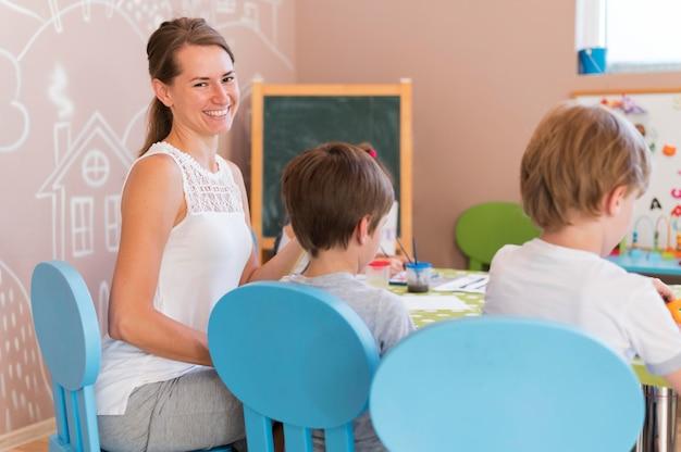 Счастливый учитель смотрит на детей Бесплатные Фотографии