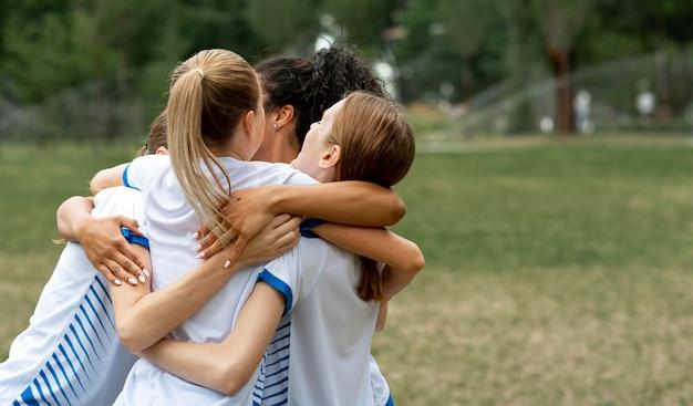 Squadra felice che abbraccia sul campo Foto Gratuite