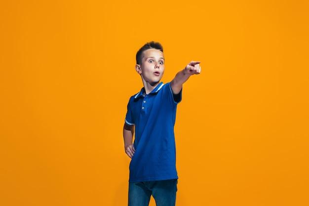 Il ragazzo adolescente felice che punta a te, ritratto closeup mezza lunghezza su sfondo arancione. Foto Gratuite