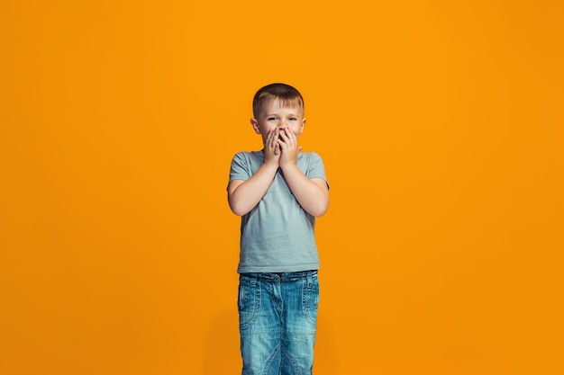 The happy teen boy standing and smiling against orange space. Free Photo