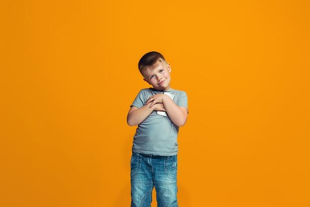 Il ragazzo adolescente felice in piedi e sorridente contro l'arancio. Foto Gratuite