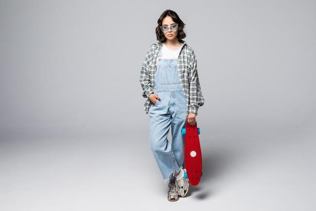 Счастливый подросток девушка держит скейтборд изолированные Бесплатные Фотографии