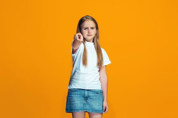 La ragazza teenager felice che indica a voi, ritratto del primo piano di mezza lunghezza su priorità bassa arancione. Foto Gratuite
