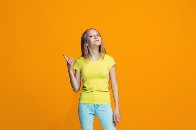 The happy teen girl standing and smiling against orange space. Free Photo