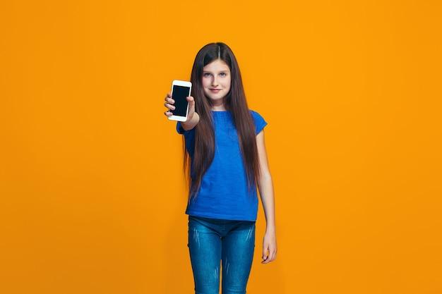 La ragazza teenager felice in piedi e sorridente contro l'arancio. Foto Gratuite