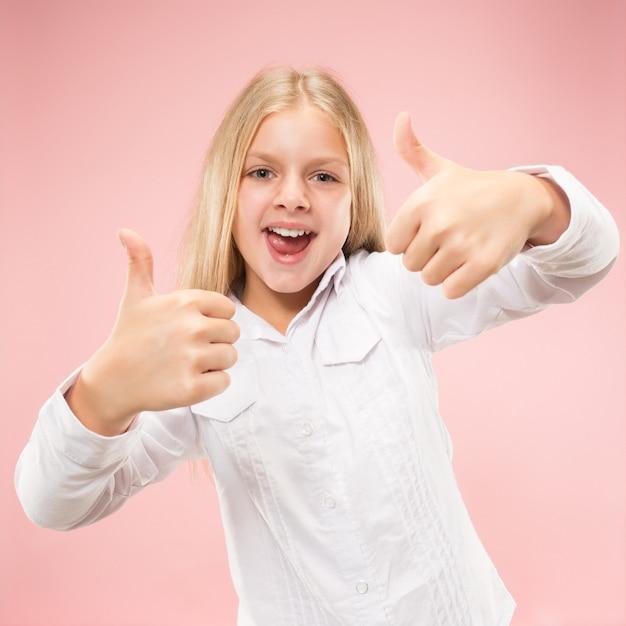 トレンディなピンクのスタジオの背景に孤立して笑顔、立っている幸せな十代の少女。美しい女性の肖像画。若いはサインokで女の子を満足させます。 無料写真