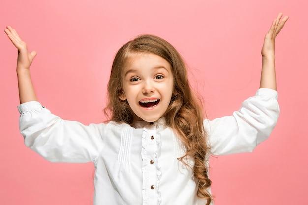 トレンディなピンクのスタジオの背景に孤立して笑顔、立っている幸せな十代の少女。 無料写真