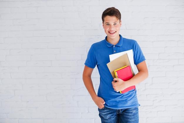 Счастливый подросток с книгами, глядя на камеру Premium Фотографии
