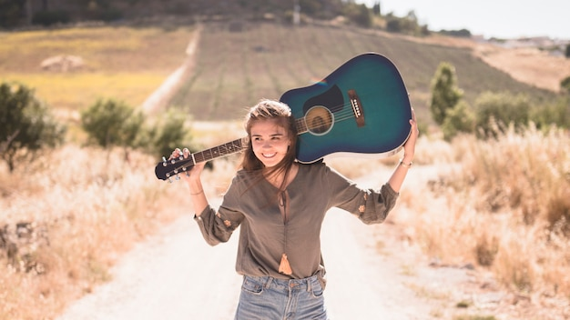Happy teenage girl holding guitar at outdoors Free Photo