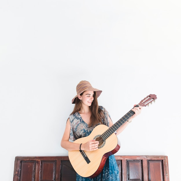 Happy teenage girl playing guitar in front of wall Free Photo