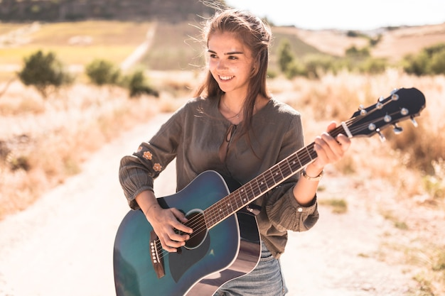 Happy teenage girl playing guitar at outdoors Free Photo