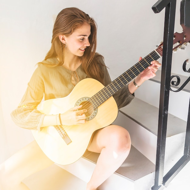 Happy teenage girl sitting on staircase playing guitar Free Photo