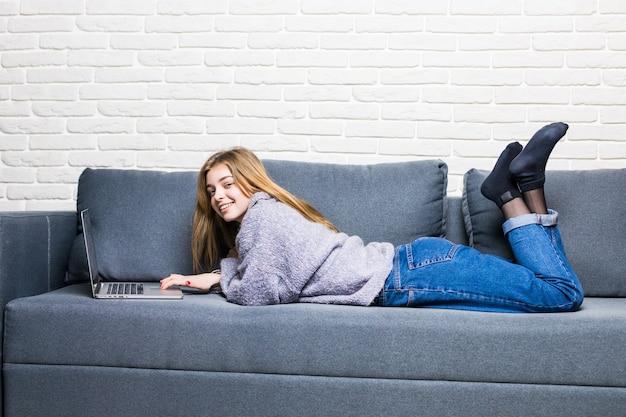 自宅のリビングルームのベッドに横になっているラップトップとラインで幸せなティーンエイジャーの女の子 無料写真