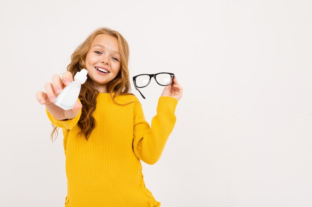 Happy teenager girl with red hair, hoody and yellow trousers holds contact lenses and glasses isolated on white Premium Photo