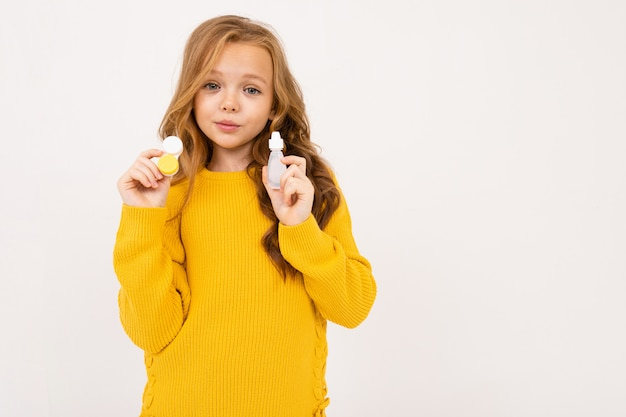 Happy teenager girl with red hair, hoody and yellow trousers holds contact lenses isolated on white Premium Photo