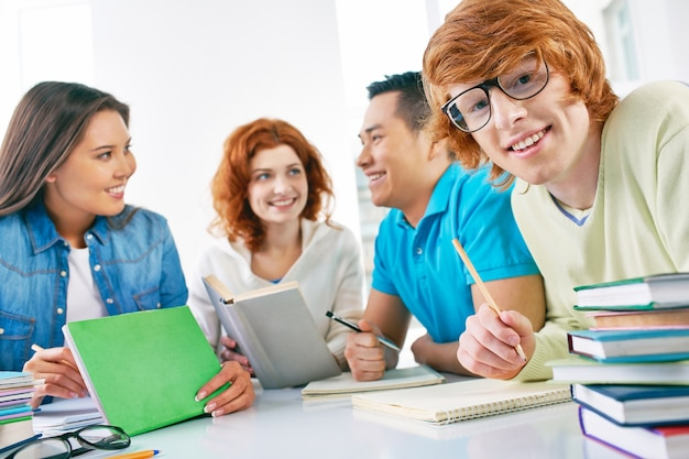 Happy teenager holding a pencil with friends background Free Photo