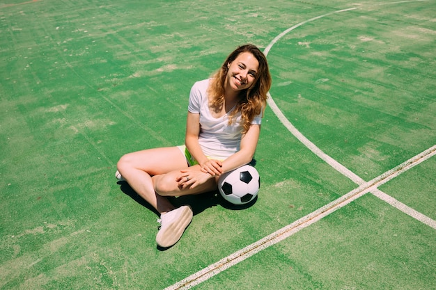 Happy teenager with ball on football pitch Free Photo
