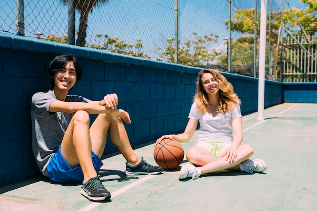 Happy teenagers sitting in basketball pitch Free Photo
