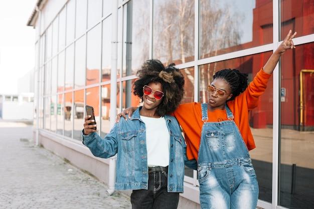 Adolescenti felici che prendono insieme un selfie Foto Gratuite