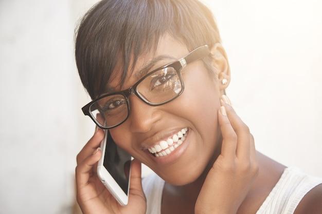 Felice concetto di conversazione telefonica. giovane signora che parla sul telefono e sul sorridere Foto Gratuite