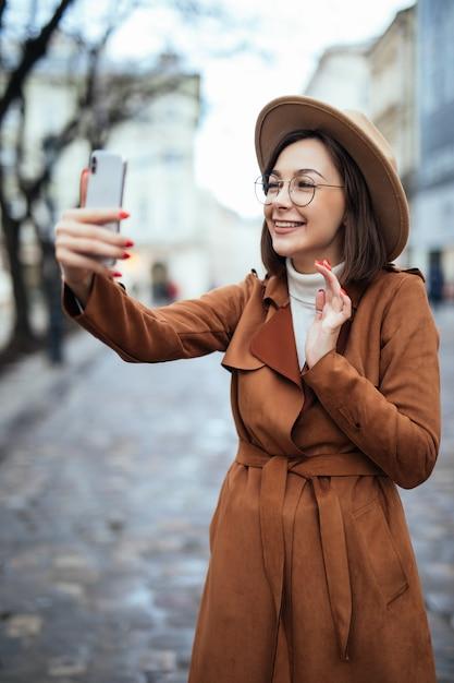 Счастливая нежная женщина принимая фото на ее телефоне в осеннем дне снаружи Бесплатные Фотографии