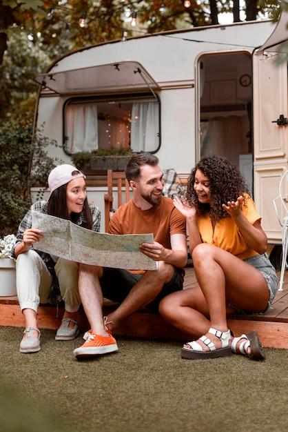 Счастливые трое друзей, глядя на карту перед фургоном Бесплатные Фотографии
