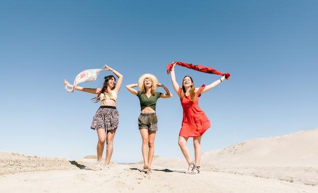 Счастливые три женщины, весело ходить на пляж. молодые люди на каникулах летом наслаждаются свободой Premium Фотографии