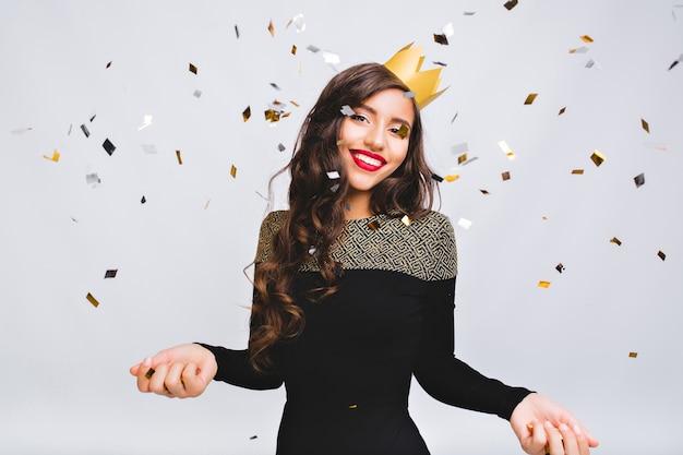 Momento felice, giovane donna sorridente che celebra il nuovo anno, vestito nero e corona gialla, festa in discoteca di carnevale felice, coriandoli scintillanti, divertirsi, sorridere. Foto Gratuite