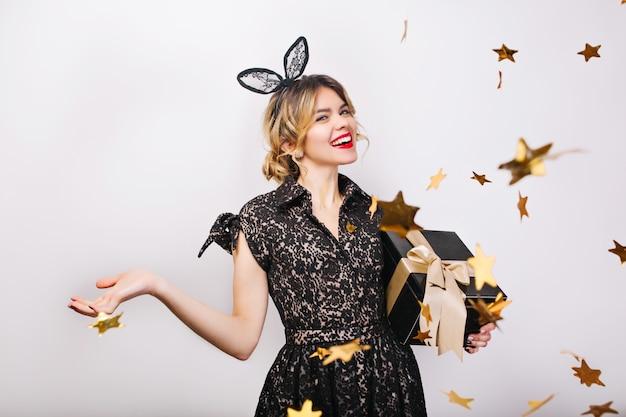 Momento felice, giovane donna sorridente con confezione regalo che celebra, vestito nero e corona, festa di buon compleanno, coriandoli d'oro scintillanti, divertirsi, sorridere. Foto Gratuite