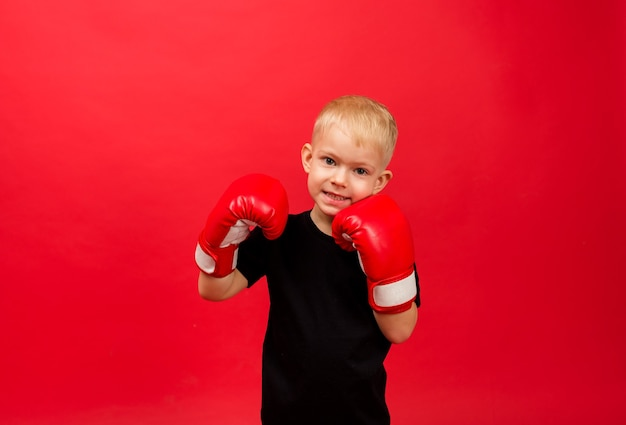 Happy toddler boy boxer in red boxing gloves on red wall Premium Photo