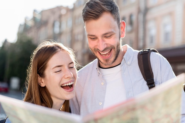 Happy tourist couple looking at map Free Photo