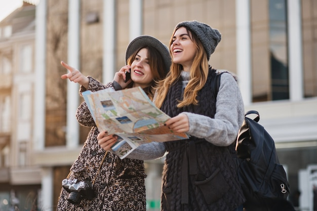 Happy travel together of two fashionable women in sunny city centre. young joyful women expressing positivity, using map, vacation with bags, cheerful emotions, good day. Free Photo