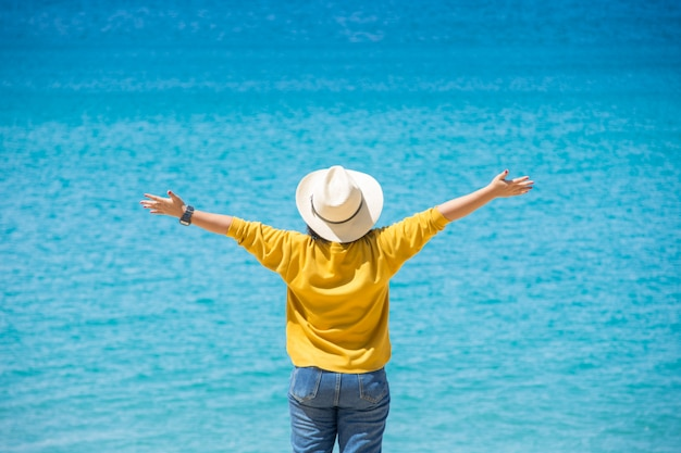 Happy travel woman stand on sand of the sea with blue sky at sunny day. Premium Photo