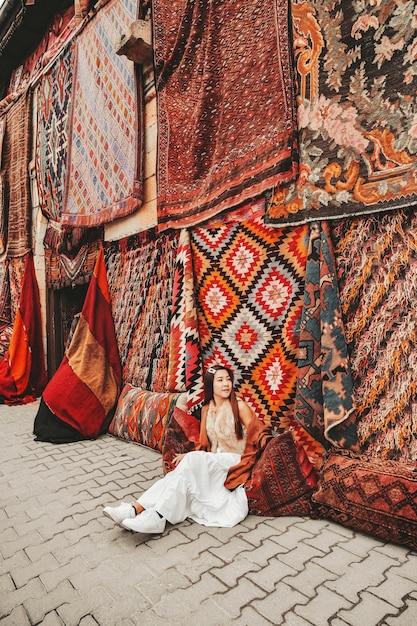 Счастливая женщина путешествия с удивительными красочными коврами в местном магазине ковров, гереме. каппадокия турция Premium Фотографии