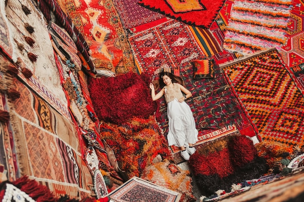 Счастливая женщина путешествия с удивительными красочными коврами в местном магазине ковров, гереме. Premium Фотографии