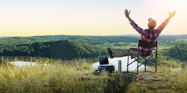 Happy traveler man and enjoying mountains nature at sunset. freedom, remote work, freelancer, techn