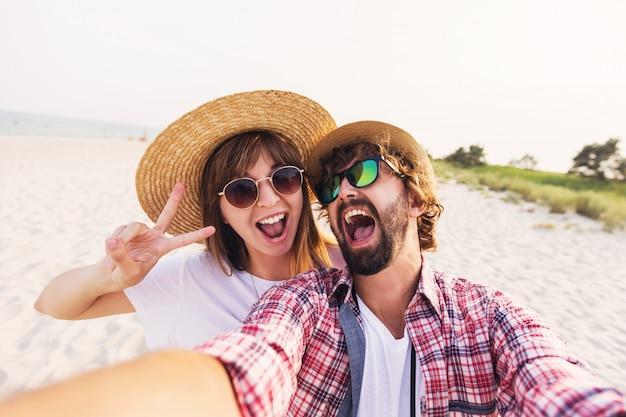 Счастливая путешествующая влюбленная пара, делающая селфи на телефоне на пляже Бесплатные Фотографии
