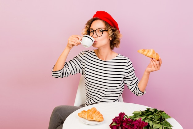 Happy traveling woman in france eating croissans with coffee, sits by the table on pink Free Photo