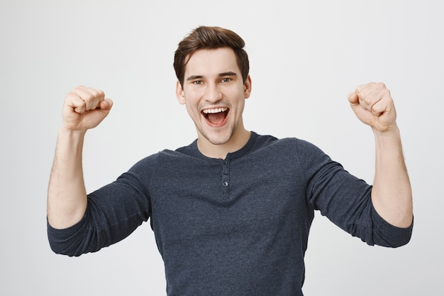 Happy triumphing man achieve goal, raise hands up and shouting yes Free Photo