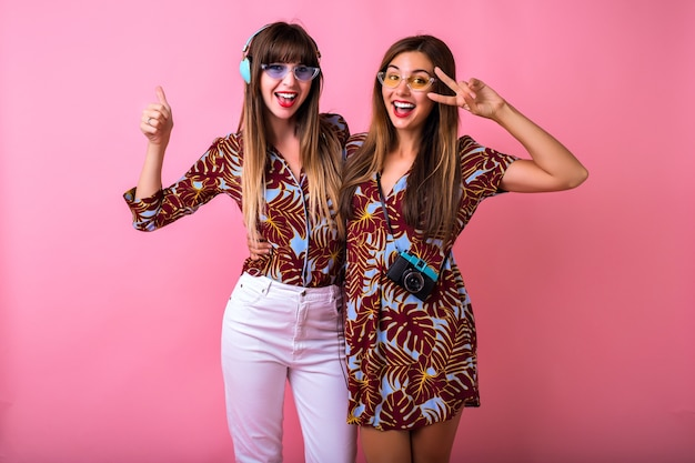 Happy two best friends sister girls having fun showing ok science, color matching tropical print clothes, colorful modern sunglasses, big headphones and vintage camera, students party. Free Photo