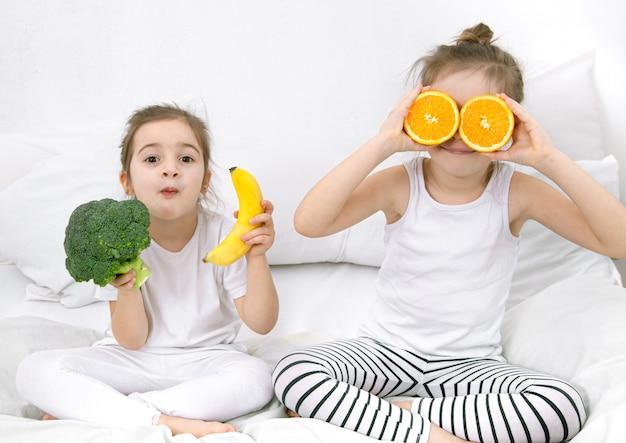 幸せな2人のかわいい子供たちが光の中で果物と野菜で遊ぶ。 無料写真