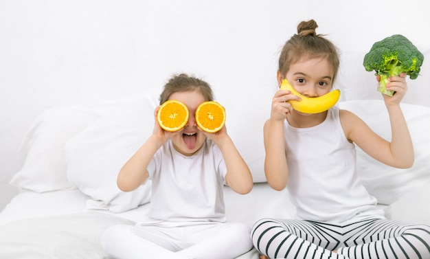 Happy two cute children playing with fruits and vegetables . Free Photo