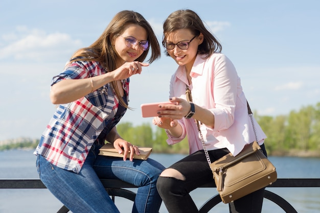 Happy two female friends watching photos Premium Photo