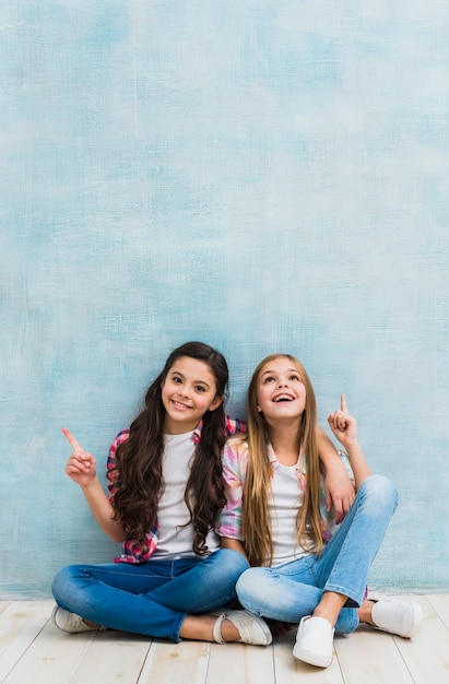Happy two girls sitting in front of blue wall pointing their finger upward Free Photo