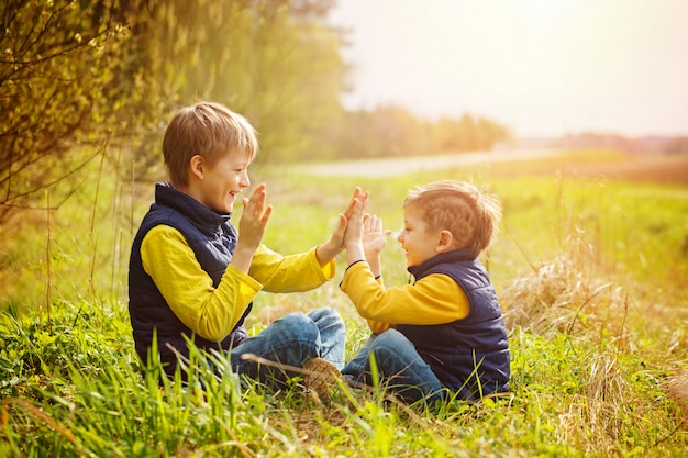 Happy two litte brothers having fun together  at the sunny day time. Premium Photo