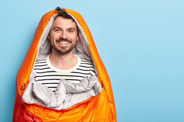 Felice vacanziere uomo con la barba lunga trascorre le vacanze vicino alle montagne in campeggio, dorme nel sacco a pelo, sorride positivamente, vestito con un maglione a righe, pone contro il muro blu Foto Gratuite