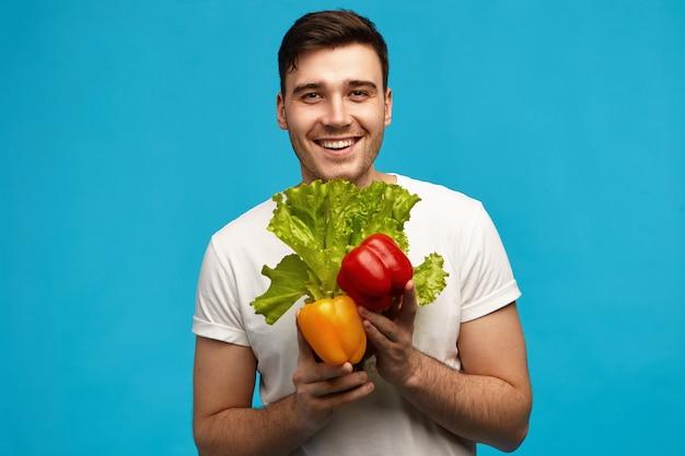 食料品店からの新鮮なカラフルな野菜とレタスを運ぶ広い輝く笑顔で筋肉のフィットボディを持つ幸せな無精ひげを生やした若い男ビーガン。ビーガン、ローフード、ダイエット 無料写真
