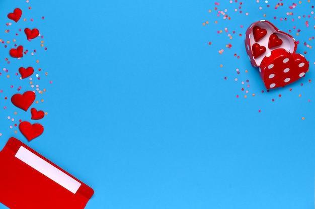 С днем святого валентина. конверт с любовным письмом и подарочной коробкой с шоколадными конфетами на синем Premium Фотографии